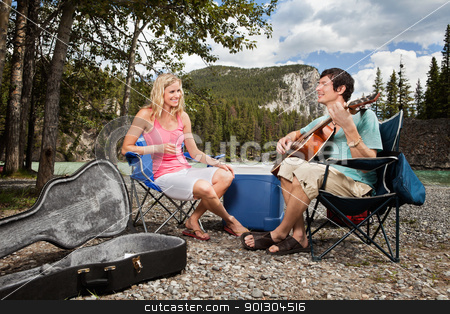 Female listening to man playing guitar stock photo, Young woman listening to man playing guitar in forest by Tyler Olson