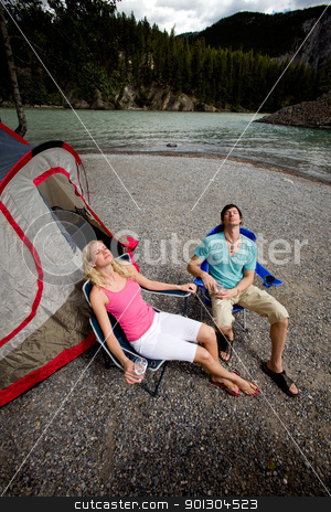 Couple Relaxing while Camping stock photo, A couple camping in the wildernerss, relaxing in the mountains by Tyler Olson