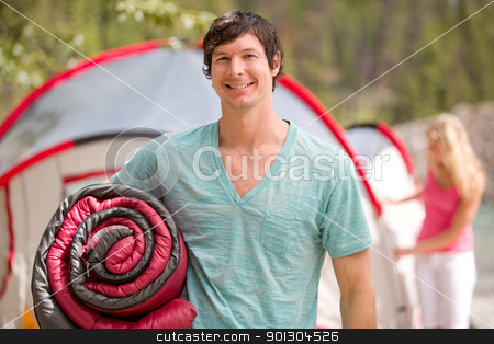 Happy Male Camper stock photo, A portrait of a happy male camper holding a sleeping bag by Tyler Olson