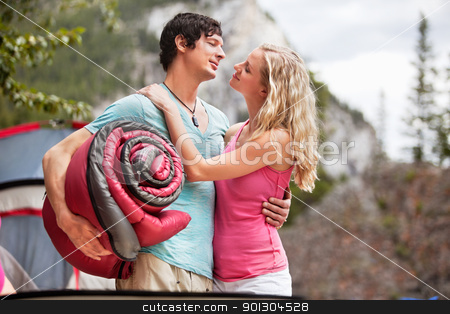Romantic couple with sleeping bag while camping stock photo, Young woman carrying sleeping bag and embracing woman while camping by Tyler Olson