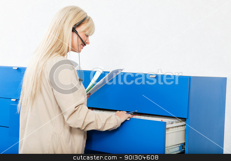 Receptionist with Medical Records stock photo, Side view of a young woman searching for documents through a file drawer by Tyler Olson