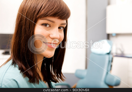 Dental Hygienist  stock photo, A portrait of a dental hygienist in front of a dental chair by Tyler Olson