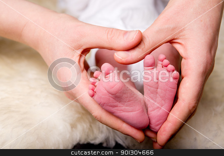 Heart Around Newborn Feet stock photo, A mother's hands in the shape of a heart around a newborn baby's feet by Tyler Olson