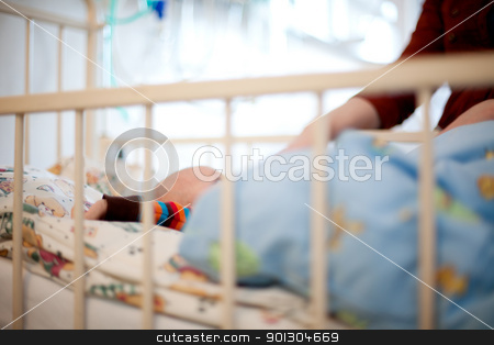 Baby in Hospital stock photo, Abstract of a young baby in a hospital bed with mother beside by Tyler Olson
