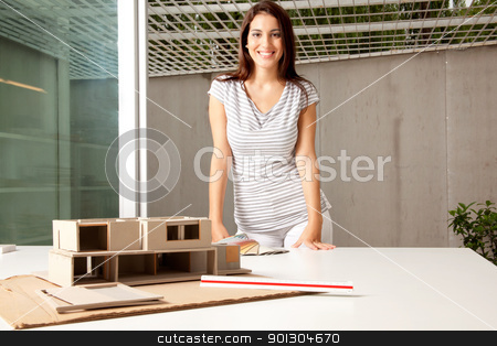 Architect with Model House stock photo, A young architect in an office with a rough model of a house by Tyler Olson