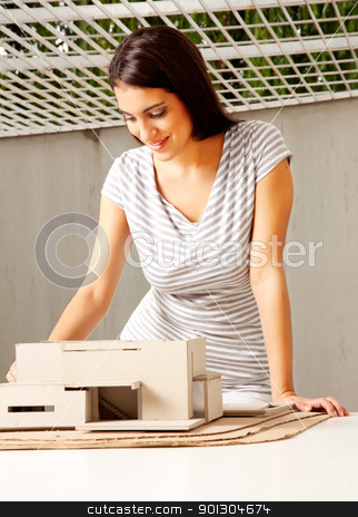 Architect with Model House stock photo, A young female architect looking over a rough model of a house by Tyler Olson