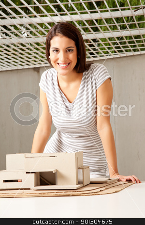 Architect stock photo, A young architect looking at the camera smiling with a rough model house by Tyler Olson