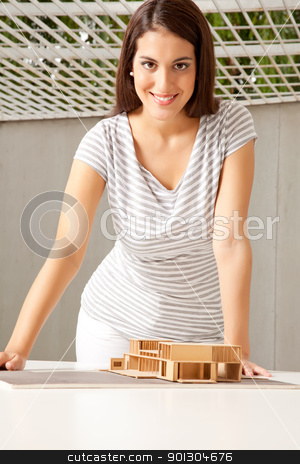 Architect Portrait stock photo, A young female architect looking at the camera with a house model on the desk by Tyler Olson