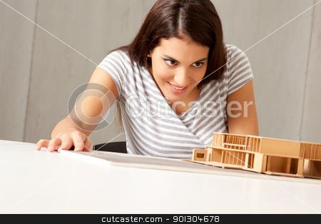 Architect Examining Model stock photo, A female architect examining a rough model house by Tyler Olson