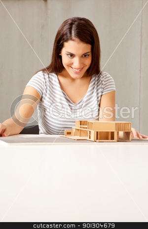 Architect with House Model stock photo, A female architect examining a rough model of a house by Tyler Olson