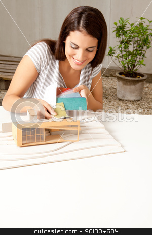 Architect with Color Swatch stock photo, A young female architect testing a color swatch on a model house by Tyler Olson