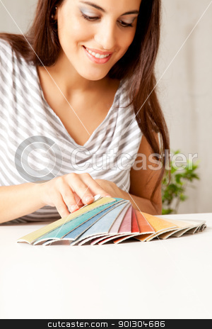 Woman looking at Color Swatches stock photo, A woman looking at various flooring color swatches by Tyler Olson