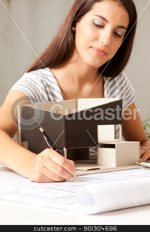 Young Female Architect with Model house stock photo, A young female architect working on blueprints with a model house by Tyler Olson