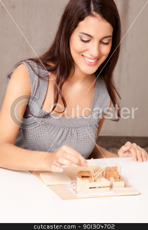 Interior Architect stock photo, A female interior architect designign a scale model house by Tyler Olson