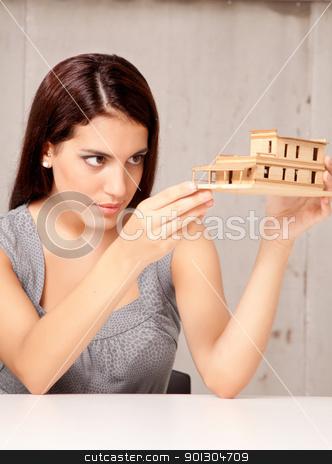 Designer Examining Model House stock photo, An architect designer examining a rough model house of wood by Tyler Olson