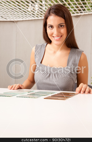 Glass Tile Samples stock photo, Woman choosing between various glass tile samples, critical focus on tiles by Tyler Olson