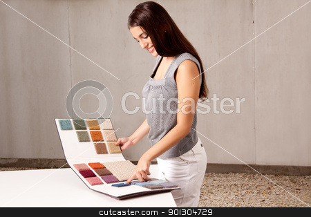 Interior Architect Choosing Rug Sample stock photo, A female interior architect or designer looking at rug samples from a catalogue by Tyler Olson
