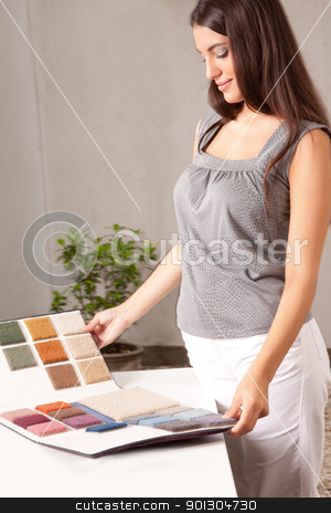 Interior Designer with Carpet Swatch stock photo, A female interior designer looking at carpet swatches in a catalogue by Tyler Olson