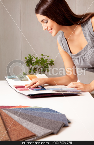 Designer with Carpet Samples stock photo, A female interior designer looking at rug samples from a catalogue by Tyler Olson