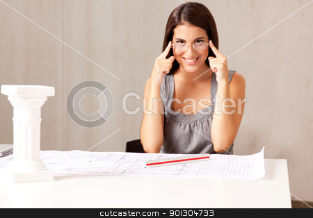 Architect at Desk stock photo, A female architect sitting at a desk with blue prints - room for copy space by Tyler Olson