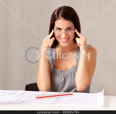 Female Architect stock photo, A portrait of a female architect looking at blueprints by Tyler Olson