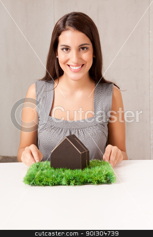 Happy House Woman stock photo, A woman holding a model house which is sitting on a turf of grass by Tyler Olson