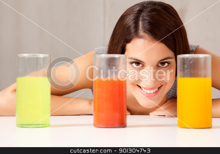 Liquid in Beaker Experiment stock photo, Three glasses with colorful liquid - woman doing experiement by Tyler Olson