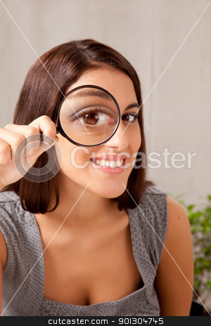 Woman with Magnifying Glass stock photo, A woman holding a magnifying glass in front of her eye and looking at the camera by Tyler Olson