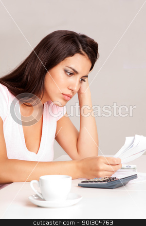 Woman Budget Planning stock photo, A woman sitting at a desk with calculator and papers planning a budget by Tyler Olson