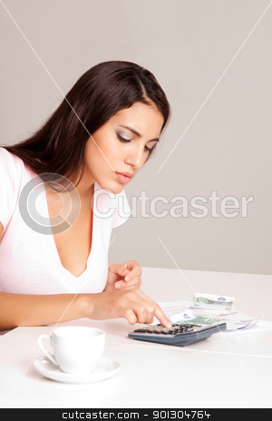 Home Finances stock photo, A woman sitting at a table with calculator, papers and coffee cup by Tyler Olson