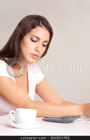 Woman Calculating Finances stock photo, A woman sitting at a desk calculating finances by Tyler Olson