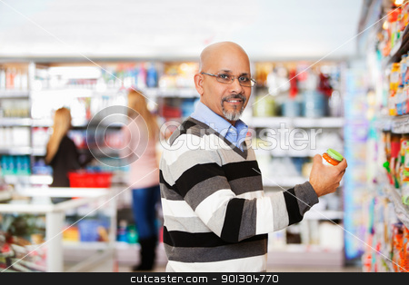 Smiling mature man shopping in the supermarket stock photo, Smiling mature man shopping in the supermarket with people in the background by Tyler Olson