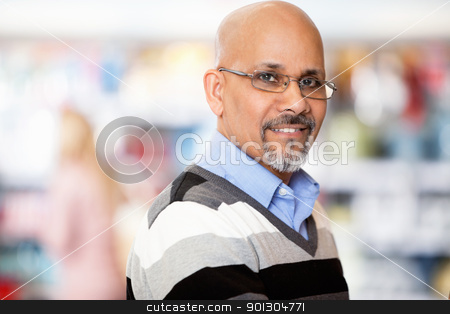 Mature man smiling while shopping stock photo, Mature man smiling while shopping in the supermarket by Tyler Olson