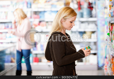 Young woman shopping in the supermarket stock photo, Young woman shopping in the supermarket with people in the background by Tyler Olson