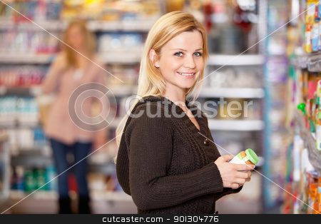 Young Woman Shopping stock photo, Portrait of a young woman smiling while shopping in the supermarket by Tyler Olson