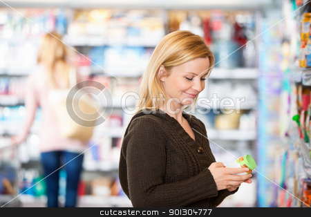 Young woman smiling while shopping stock photo, Young woman smiling while shopping in the supermarket with people in the background by Tyler Olson