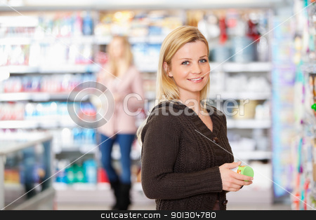 Grocery Store Smile stock photo, Young woman smiling while holding goods in the supermarket with people in the background by Tyler Olson