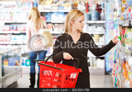 Shopping Woman stock photo, Young woman carrying basket while shopping in the supermarket by Tyler Olson
