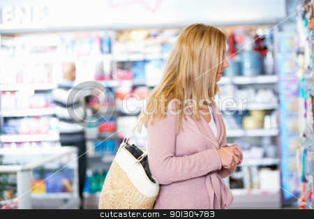 Faceless Woman in Grocery Store stock photo, Young woman looking at goods in the supermarket with people in the background by Tyler Olson