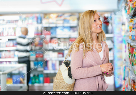 Woman in Grocery Store stock photo, Young woman smiling while looking at goods in the supermarket with people in the background by Tyler Olson