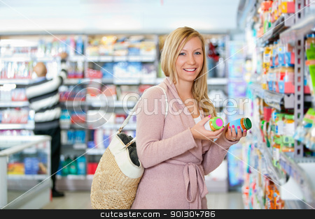 Portrait of a happy young woman holding jar stock photo, Portrait of a happy young woman holding jar in the supermarket by Tyler Olson