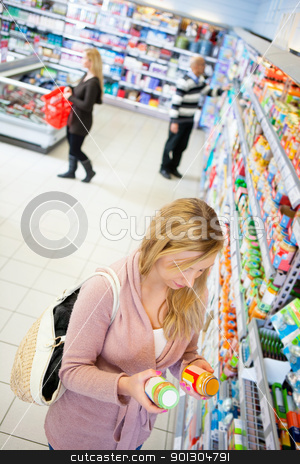 Woman Comparing Prices stock photo, High angle view of a woman comparing products in a grocery store by Tyler Olson