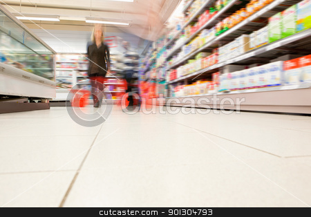 Blurred view of people in supermarket stock photo, Blurred view of people in supermarket while shopping by Tyler Olson