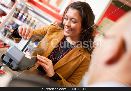 Shop assistant smiling while swiping credit card in supermarket stock photo, Shop assistant smiling while swiping credit card in supermarket with customer in the foreground by Tyler Olson