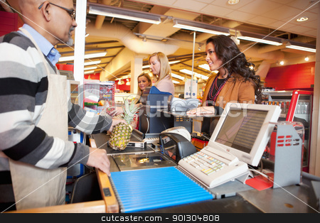 Grocer Store Checkout stock photo, Shop assistant with customer in supermarket by Tyler Olson