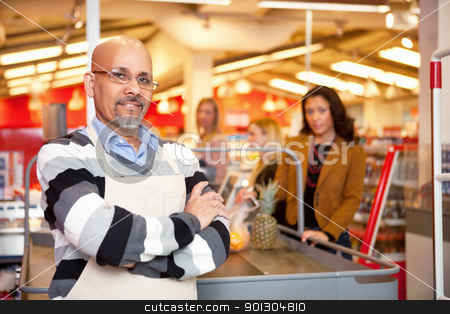 Grocery Store Cashier stock photo, Portrait of a grocery store cashier standing at a checkout counter by Tyler Olson