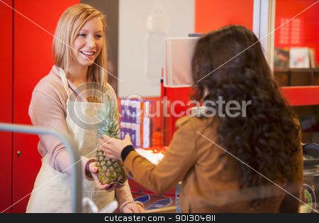 Happy shop assistant with customer in supermarket stock photo, Happy shop assistant with customer in supermarket holding pineapple by Tyler Olson
