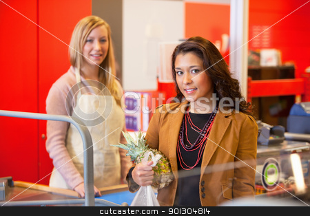 Supermarket Store Customer stock photo, Portrait of a customer holding pineapple with shop assistant in the background by Tyler Olson