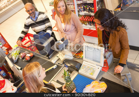 Grocery Store Line stock photo, High angle view of cashier with a line of people at the check-out counter by Tyler Olson