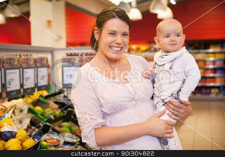Portrait of Mother and Child in Store stock photo, Closeup of a happy mother carrying child in supermarket by Tyler Olson